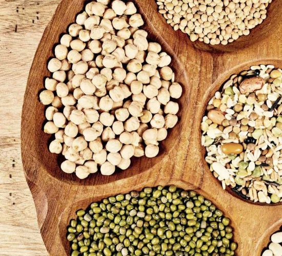 Wooden bowl of various legumes (chickpeas, lentils, green lentils, green mung,beans) on wooden background